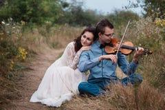 El violinista y la mujer en el vestido blanco, hombre joven juega en el violín la naturaleza del fondo Imagen de archivo