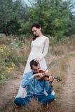 El violinista y la mujer en el vestido blanco, hombre joven juega en el violín la naturaleza del fondo Imagen de archivo libre de regalías
