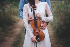 El violinista y la mujer en el vestido blanco, hombre joven juega en el violín la naturaleza del fondo Fotos de archivo
