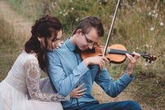 El violinista y la mujer en el vestido blanco, hombre joven juega en el violín la naturaleza del fondo Imagenes de archivo