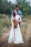 El violinista y la mujer en el vestido blanco, hombre joven juega en el violín la naturaleza del fondo Foto de archivo
