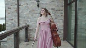 El violoncelista de sexo femenino feliz camina en el balcón y los juegos en el violoncelo metrajes