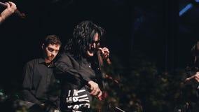 El violoncelista fresco en un traje negro juega grande en etapa como parte de una banda de rock ella es muy emocional y artística metrajes