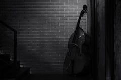 El violoncelo adornó cerca de la pared de ladrillo Imagen de archivo libre de regalías