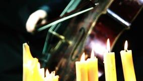 El violoncelo de madera viejo que juega en velas se enciende almacen de metraje de vídeo