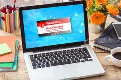 El virus detectó la advertencia en una pantalla del ordenador portátil en un escritorio de oficina Imagen de archivo