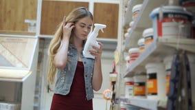 El visitante femenino de la tienda está tomando la botella del estante y está leyendo en pasillo con los tintes almacen de video