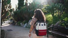 El visitante femenino está caminando dentro de jardín tropical con las plantas exóticas del cactus metrajes