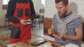 El visitante masculino de pequeños restaurantes está pagando su cuenta por la tarjeta al camarero metrajes