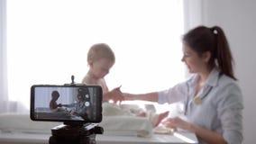 El vlog de Internet, pediatra de sexo femenino del vlogger popular se alivia en cámara durante el examen médico del niño adentro almacen de video