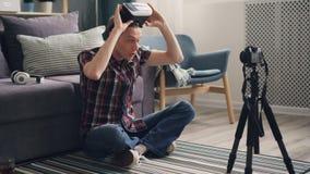 El vlogger feliz del hombre joven está compartiendo su experiencia con los vidrios de la realidad virtual que registran el vídeo  almacen de metraje de vídeo