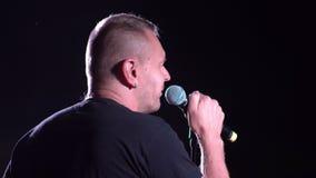 El vocalista canta en etapa con el micrófono 4k almacen de video
