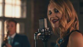 El vocalista en vestido que brilla intensamente se realiza en etapa en el micrófono Estilo retro elegancia almacen de video