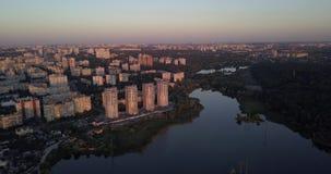El volar bajo encima en el centro de la ciudad con opiniones de la puesta del sol del paisaje urbano pixeles de 4k 4096 x 2160 metrajes