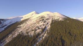El volar cerca de las montañas rocosas cubiertas con nieve almacen de metraje de vídeo