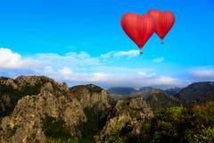 El volar de aerostación de la forma del corazón sobre la montaña fotografía de archivo