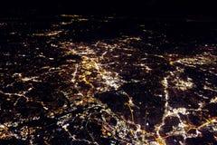 El volar en la noche sobre ciudades abajo Fotografía de archivo libre de regalías