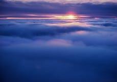 El volar entre la nube en la puesta del sol Foto de archivo libre de regalías