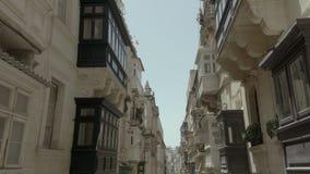 El volar liso del abejón detrás a través de la calle vieja hermosa, La Valeta, Malta Viejo, ventanas del vintage, balcones - 4K almacen de metraje de vídeo