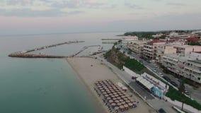 El volar sobre ciudad de vacaciones con el muelle Nea Kallikratia, Grecia almacen de metraje de vídeo