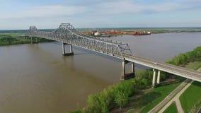 El volar sobre el río Misisipi y el puente conmemorativo de los veteranos en New Orleans Fábrica de la refinería del alúmina de G metrajes