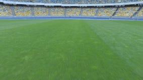 El volar sobre hierba en una pequeña altura dentro del estadio vacío moderno enorme almacen de video