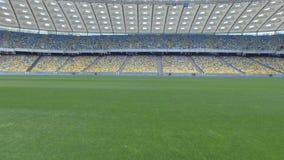 El volar sobre hierba en una pequeña altura dentro del estadio vacío moderno enorme almacen de metraje de vídeo