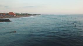 El volar sobre la playa del océano con las personas que practica surf en la puesta del sol metrajes