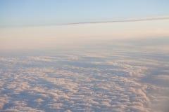 El volar sobre las nubes en el paisaje de la puesta del sol de un aeroplano Imagen de archivo libre de regalías