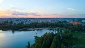 El volar sobre los árboles y el lago en la ciudad en el amanecer - phot aéreo Fotos de archivo