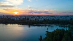 El volar sobre los árboles y el lago en la ciudad en el amanecer - phot aéreo Fotos de archivo libres de regalías