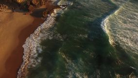 El volar sobre los acantilados del océano en la puesta del sol Guincho aéreo Portugal metrajes