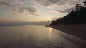 El volar sobre el mar a lo largo de la costa en la puesta del sol metrajes