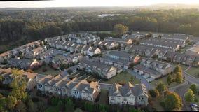 El volar sobre nuevas propiedades horizontales y construcciones en Atlanta suburbana durante puesta del sol almacen de video