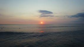 El volar sobre olas oceánicas y personas que practica surf hermosas en la puesta del sol Cantidad aérea almacen de metraje de vídeo