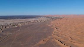 El volar sobre una duna del desierto cerca del pueblo Merzouga en Marruecos con el abejón desde arriba de (aéreo) almacen de video