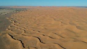 El volar sobre una duna del desierto cerca del pueblo Merzouga en Marruecos con el abejón desde arriba de (aéreo) metrajes