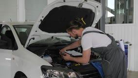 El voltímetro en manos, mecánico de automóviles mide voltaje de la batería almacen de video