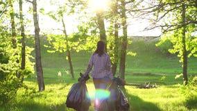 El voluntario de la muchacha en camisa con los bolsos de basura plásticos en el parque va en la puesta del sol almacen de video