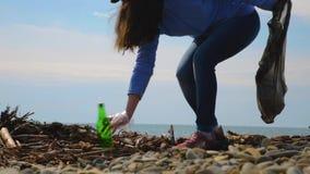 El voluntario femenino joven recoge la basura en la playa Protecci?n del medio ambiente y responsabilidad Eco y d?a de concepto d almacen de video