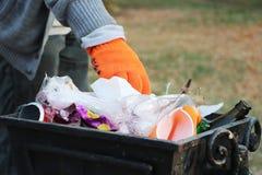 El voluntario limpia la basura en el parque y la lanza en el bote de basura foto de archivo libre de regalías