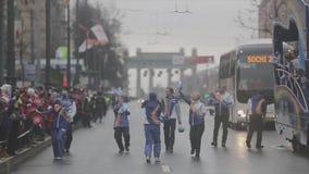 El voluntario que camina da el pom del pom a la gente megabus Raza de retransmisión de llama olímpica de Sochi en St Petersburg almacen de metraje de vídeo