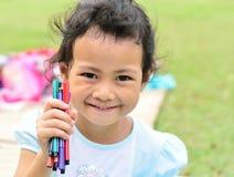 El volver a la escuela: Niña que sostiene plumas del color Foto de archivo