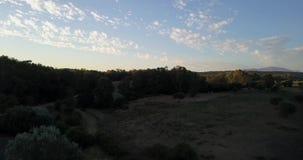 El vuelo aéreo sobre las colinas y el polo colocan en la puesta del sol almacen de video