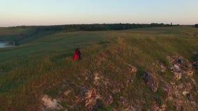 El vuelo aéreo sobre pares en el amor que camina en la orilla del río afila Mujer en vestido rojo asombroso Hombre en negro Puest metrajes