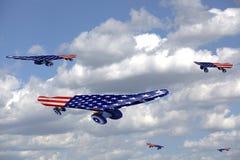 El vuelo anda en monopatín con la bandera de los E.E.U.U. en un cielo azul y las nubes Fotos de archivo libres de regalías