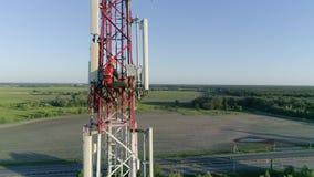 El vuelo del abejón alrededor de la torre al aire libre de la estación base del repetidor, contratista trabaja en sistema de la a
