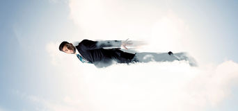El vuelo del hombre de negocios le gusta un super héroe en nubes en el cielo Fotografía de archivo libre de regalías