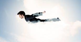 El vuelo del hombre de negocios le gusta un super héroe en nubes en el cielo Imágenes de archivo libres de regalías