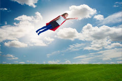 El vuelo del niño del super héroe en concepto ideal imagen de archivo libre de regalías